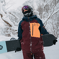 Person posing in snow wearing Burton jacket and holding snowboard behind his back