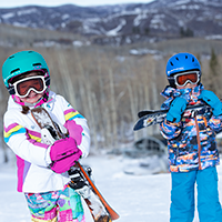 Kids dressed in winter clothing, helmets, and goggles standing in snow with mountain in background
