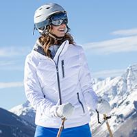 Woman smiling looking away wearing a white Obermeyer ski jacket