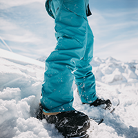 Legs of a person wearing blue snowboard pants in the snow