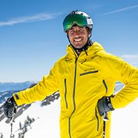 Man posing on a mountain wearing a ski jacket